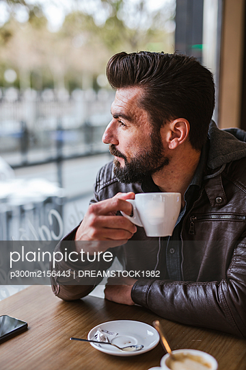 Bearded mature man in a coffee shop looking out of window - p300m2156443 by DREAMSTOCK1982
