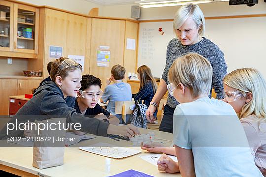 Schoolchildren with teacher in classroom - p312m2119872 by Johner