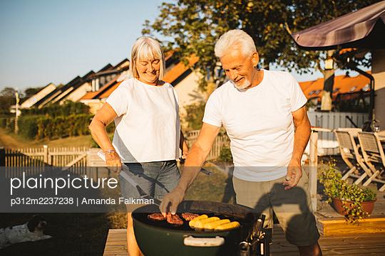 Couple preparing food on grill in garden - p312m2237238 by Amanda Falkman