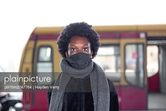 Junge dunkelhäutige Frau vor einem Bus, Portrait - p975m2247764 von Hayden Verry