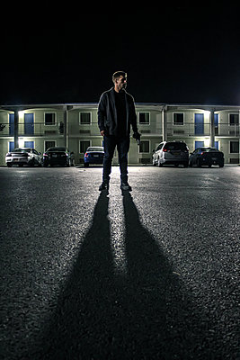Man in a street at night - p1019m1424633 by Stephen Carroll