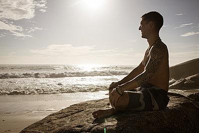 Mann meditiert auf dem Strand in der Abendsonne - p1640m2261013 von Holly & John