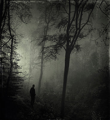 Man standing in gloomy forest - p300m1084843 by Dirk Wüstenhagen