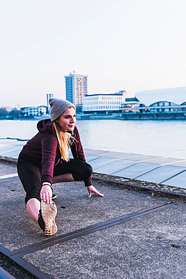 Young woman stretching at the riverside in the city - p300m1568510 by Uwe Umstätter