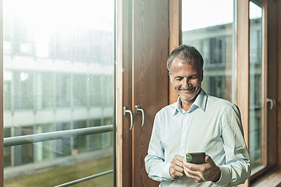 Smiling male entrepreneur using smart phone while standing at window in office - p300m2266293 by Gustafsson