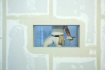 A house painter holding a trowel, seen through window hole in a newly constructed wall - p301m799831f by Caspar Benson