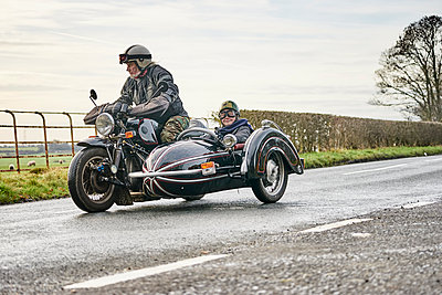 Senior man and grandson riding motorcycle and sidecar along rural road - p429m1226888 by GS Visuals