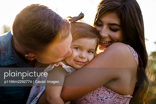 Mom & Dad Snuggling One Year Old at Sunset in San Diego - p1166m2292774 by Cavan Images