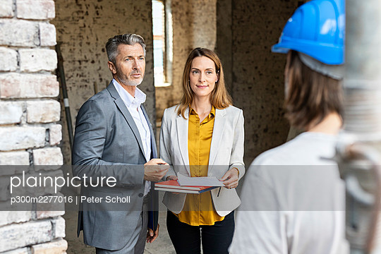 Male and female architect talking with construction worker at site - p300m2277016 by Peter Scholl