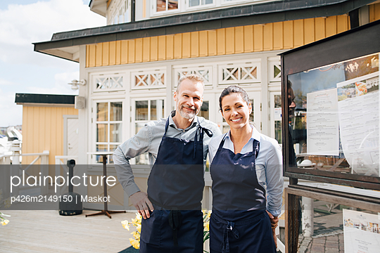 Portrait of smiling owners outside of restaurant - p426m2149150 by Maskot