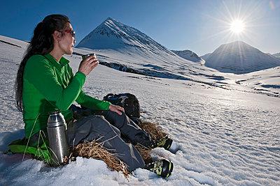 woman having coffee break while hiking in Iceland - p1166m2269479 by Cavan Images