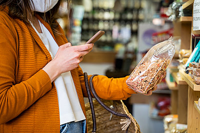 Young woman photographing organic food package in grocery store - p300m2264465 by VITTA GALLERY