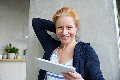 Happy woman with digital tablet against column at home - p300m2266092 by Jo Kirchherr