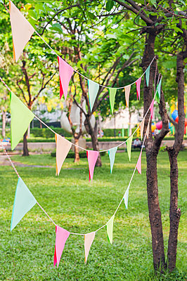Bunting in park for birthday party - p352m2039862 by Anna Larsson