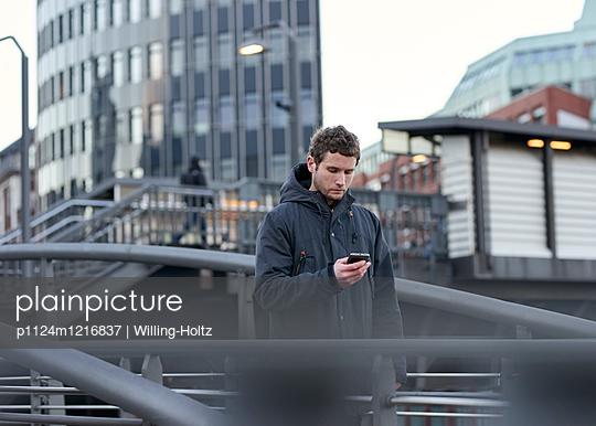 Mann mit Smartphone in der Stadt - p1124m1216837 von Willing-Holtz