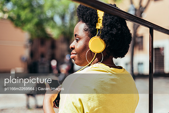Rear view of a black girl with afro hair and hoop earrings listening to music with her cell phone and yellow headphones in an urban space in the city. - p1166m2269564 by Cavan Images