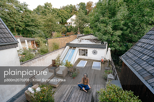 Woman with headphones sitting on terrace doing yoga exercise - p300m2070208 by Kniel Synnatzschke