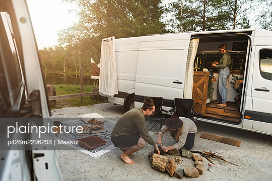 Young male friends arranging rocks for campfire during vacation - p426m2296293 by Maskot
