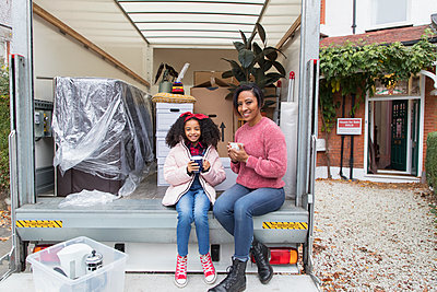 Portrait happy mother and daughter drinking tea at back of moving van, moving house - p1023m2087958 by Robert Daly
