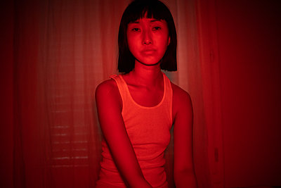 Asian woman in lingerie bathed in red light - p1321m2211725 by Gordon Spooner