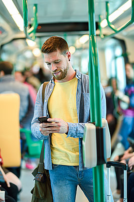 Young man in a subway train looking at his smartphone - p300m1587705 von Javier Sánchez Mingorance