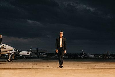Businessman walking on airfield - p586m1208653 by Kniel Synnatzschke
