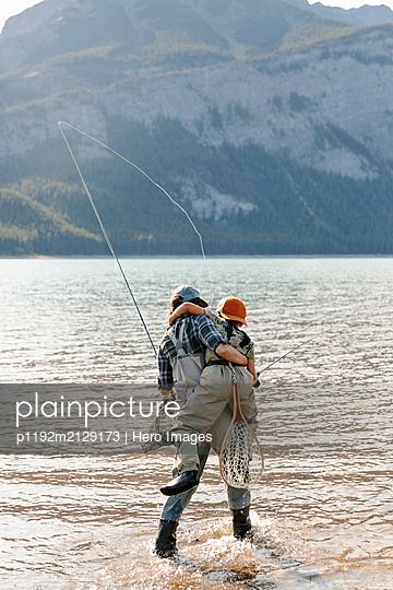 Mother and son fly fishing in lake - p1192m2129173 by Hero Images