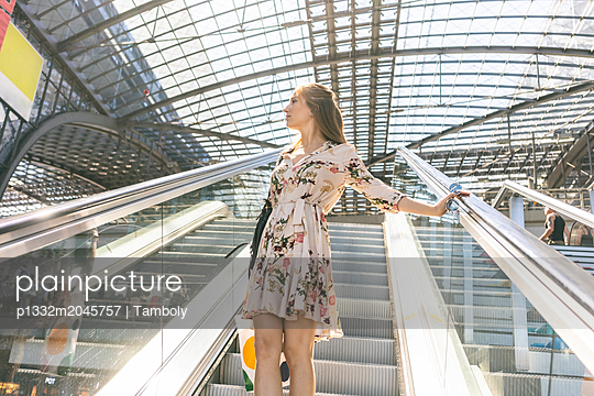 Woman using moving stairs at train station in Berlin - p1332m2045757 by Tamboly