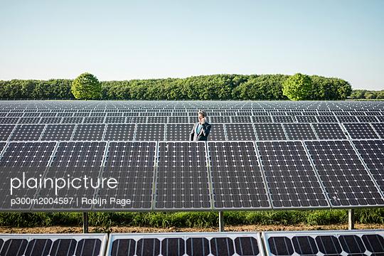 Mature man using smartphone standing on panel in solar plant - p300m2004597 von Robijn Page