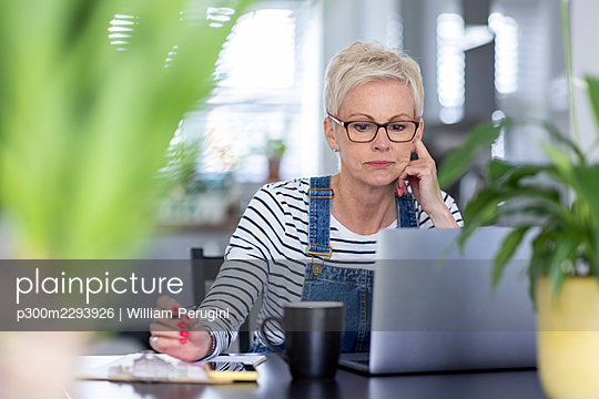 Female professional wearing eyeglasses looking at laptop in home office - p300m2293926 by William Perugini
