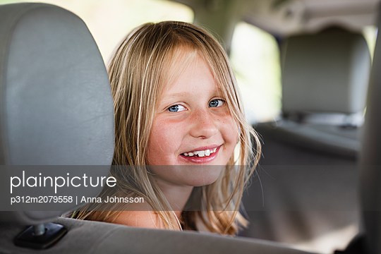 Smiling girl in car - p312m2079558 by Anna Johnsson