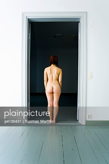 Nude woman standing in the doorway - p4130431 by Tuomas Marttila