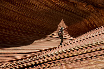 Hiker with backpack standing on Marble Canyon during sunny day - p1166m1509076 by Cavan Images