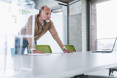 Casual mature businessman leaning on conference table in office - p300m1562268 by Uwe Umstätter