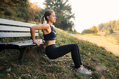 Young woman during workout on a bench - p300m2084072 by Sebastian Dorn