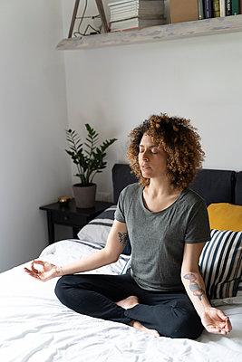 Woman practicing yoga, sitting on bed, meditating - p300m2103484 by Francesco Morandini