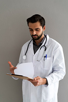 Male doctor reading medical report in front of wall - p300m2275466 by Giorgio Fochesato