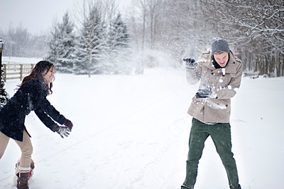 Young couple having snowball fight in snow covered forest, Ontario, Canada - p429m2050873 by Sara Monika