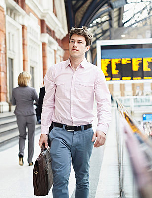 Casual businessman walking with briefcase - p429m803592f by Liam Norris