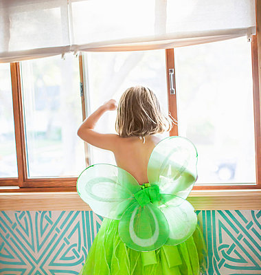Back view of child in green fairy costume looking out window - p429m819582 by Angela Bird