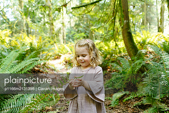 Portrait of a young girl playing with a fern on a hike - p1166m2131398 by Cavan Images