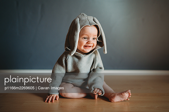 Adorable smiling baby wearing a bunny costume to celebrate Easter - p1166m2269605 by Cavan Images