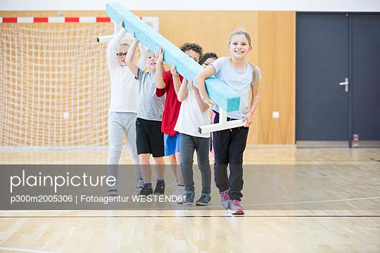 Pupils carrying balance beam in gym class - p300m2005306 von Fotoagentur WESTEND61