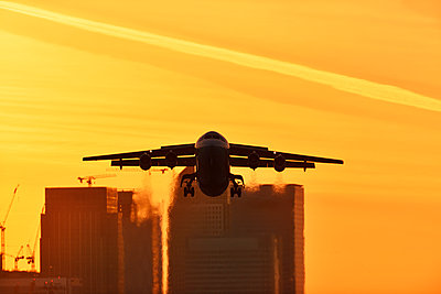 Airliner flying over London skyscrapers - p1048m2024239 by Mark Wagner