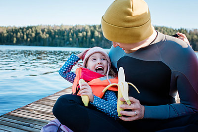 father and daughter eating fruit laughing at the beach on vacation - p1166m2163478 by Cavan Images