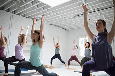 Women practicing yoga warrior one pose in yoga class - p1192m1583325 by Hero Images