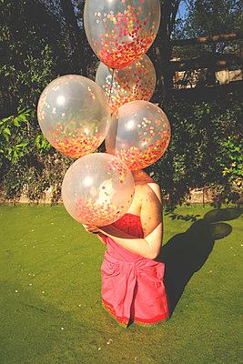 Woman in pink dress in a pond with balloons - p1521m2272080 by Charlotte Zobel