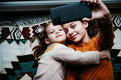 Girl embracing sister while taking selfie through mobile phone at home - p300m2225325 by Eva Blanco