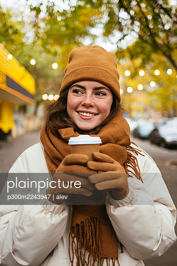 Smiling woman in warm clothing holding disposable coffee cup on sidewalk - p300m2243947 by alev