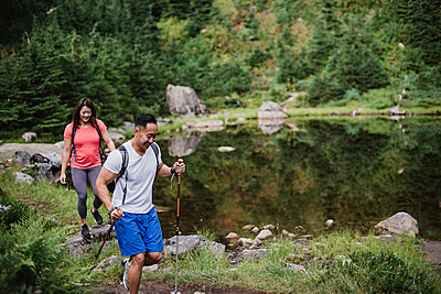 Couple hiking along lake in woods - p1023m2073985 by Jarusha Brown